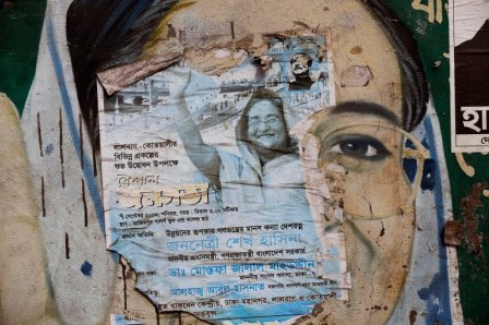 A torn election campaign poster of Bangladesh's Prime Minister Sheikh Hasina is seen on top of a mural depicting her in Dhaka. Image Credit: Reuters.
